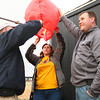 4-2-14<br /> Ryan Beining memorial service<br /> Ryan Beining's uncle Kris Beining, and parents Anita and Nate Beining, light a paper lantern near Taylor Intermediate's baseball field, which was named Ryan's Field.<br /> KT photo | Kelly Lafferty