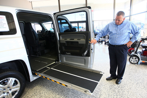4-23-14<br /> Adams Auto Group<br /> Brian Adams of Adams Auto Group demonstrates how to lower the ramp of a MV-1, a wheelchair accessible vehicle.<br /> Kelly Lafferty | Kokomo Tribune