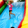 7-31-13  <br /> YMCA's Camp Tycony end of the summer camp season carnival featured gaves for the kids and elephant ears. Hannah Moore, 8 running down the inflatable obstacle coarse slide with Devin Lee, 3, making his way off.<br />   KT photo | Tim Bath