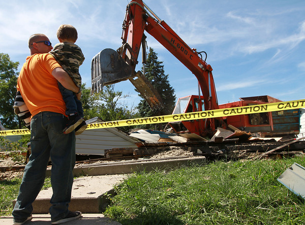 8-17-12 and 8-18-12<br /> Wounded Warrior house destruction<br /> U.S. Army Specialist, Anthony Walton holds his 3-year-old son Noah on the front steps which used to lead to his home. The house was demolished and a new one will be built in its place.<br /> KT photo | Kelly Lafferty