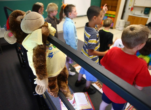 8-30-12<br /> Taylor Primary School 3rd graders carry a stuffed monkey around the school in place of classmate Alana Johnson who is out sick with Lukemia. Music class afforded Alana special priviledges to hang on the riser's bars.<br /> KT photo | Tim Bath