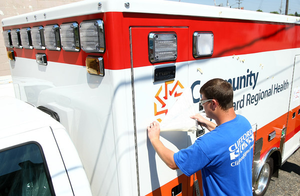 8-24-12<br /> James Elkins from Clifford Signs puts the finishing touches on the decals of a new ambulance the Community Howard Regional Health purchased.<br /> KT photo | Tim Bath