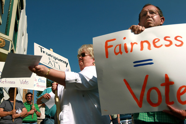 8-30-12<br /> Delphi rally<br /> David Howell (right) holds up a sign during the Delphi salaried retirees rally at the courthouse on Thursday afternoon.<br /> KT photo | Kelly Lafferty