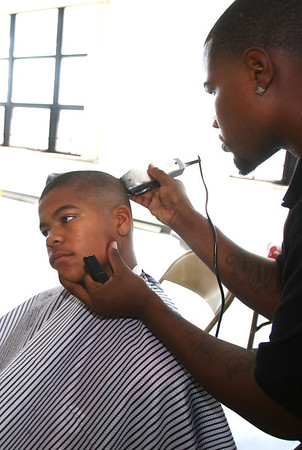 8-6-12<br /> Back to school haircuts provided free of charge at Carver Community Center by Kut Above and MC Barber Shop. Michael Stewart, 14, getting a haircut from James Warren from Kut Above.<br /> KT photo | Tim Bath