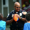 8-5-14<br /> National Night Out<br /> Major Brian Seldon takes a break from throwing a football to talk to 10-year-old Isaiah Brown (left) and watch as 9-year-old Jaiden McClain places a sticker on his uniform in Garden Square during National Night Out.<br /> Kelly Lafferty | Kokomo Tribune