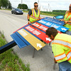 8-11-14<br /> Workers from Michiana Contracting Inc. out of Plymouth, Indiana, installing signs throughout the city. Nick Lunetta and David Sills lift a sign while Jason Ball pulls a saw horse out from under it along SR 26.<br /> Tim Bath | Kokomo Tribune