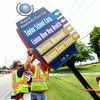 8-11-14<br /> Workers from Michiana Contracting Inc. out of Plymouth, Indiana, installing signs throughout the city. Nick Lunetta and David Sills lift a sign while Jason Ball guides it onto the base bolts along SR 26 aproaching US 931.<br /> Tim Bath | Kokomo Tribune