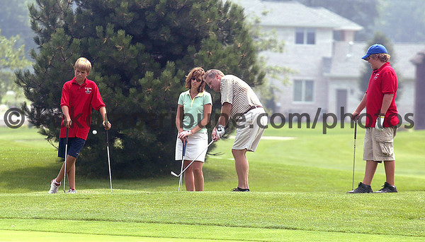 8/10/05<br /> KT photo | Erik Markov<br /> John Fountain golfs with his wife Lori and their two sons, Benji, left, and Patrick during the YMCA golf tournament at Wildcat Creek Course Wednesday, August 10, 2005.