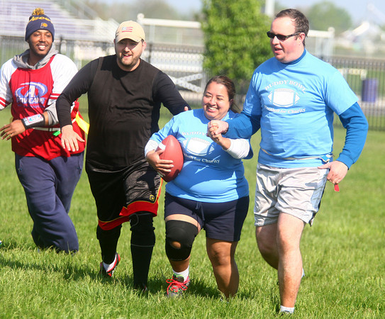 5-17-14<br /> Buddy Bowl<br /> With the help of Daniel Dean and Jeremiah Belk, Claudia Villalobos runs the football to make a touchdown during one of the Buddy Bowl flag football games on Saturday morning.<br /> Kelly Lafferty | Kokomo Tribune