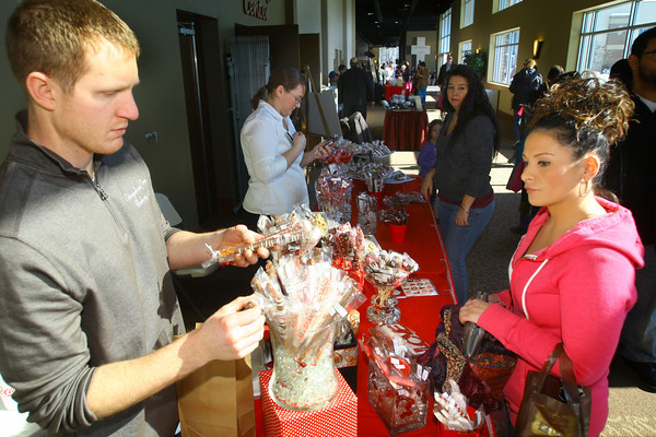 2-8-14   ---  Matt Gaines from the Gingerbread House Bakery picks out chocolate covered pretzels for Erika Salinas at the Samaratian Caregivers' Chocolate Celebration. -- <br />   KT photo | Tim Bath