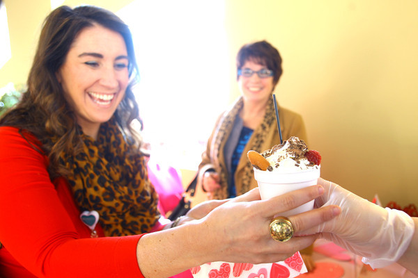 2-8-14   ---  Lynnsey Bell reaches for a Nutella Hot Chocolate with toppings from Bona Vista at the Samaratian Caregivers' Chocolate Celebration. -- <br />   KT photo | Tim Bath