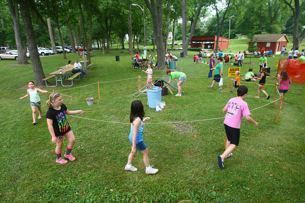 6-25-14<br /> Craft Fest<br /> Kids walk around the perimeter of the candle making station as they from candles with wax and water at the Craft Fest in Highland Park.<br /> Kelly Lafferty | Kokomo Tribune