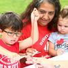 6-25-14<br /> Craft Fest<br /> 5-year-old Brogen Salinas cuts a piece of dyed yarn in half as his grandma Debby Rayn, and his 2-year-old sister Arye Salinas watch him tie dye a t-shirt at the Craft Fest.<br /> Kelly Lafferty | Kokomo Tribune