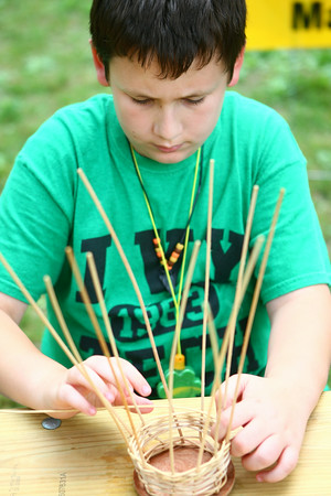 6-25-14<br /> Craft Fest<br /> Kolton Mickle, 11, tries his hand at basket weaving in Highland Park during the Craft Fest on Wednesday.<br /> Kelly Lafferty | Kokomo Tribune