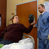 12-31-12<br /> Walton rehab<br /> Rhonda hands Anthony's helmet to him before he goes in the restroom. Although Anthony doesn't like wearing it, he has to wear it to protect his skull (since he's had surgery to get part of it removed) when he walks around.<br /> KT photo | Kelly Lafferty