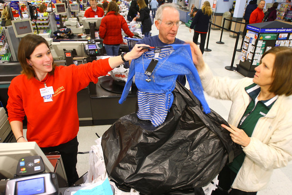 12-17-13   ---  Goodfellows shopping at Meijer on Tuesday evening. Cashier Loraine York hands items to volunteers Mark Underwood, goodfellows board member, and Vicki Boles, Kokomo Roadrunners, to bag up.<br />   KT photo | Tim Bath