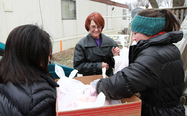 12-25-13<br /> Kokomo Urban Outreach Annual Christmas Blitz<br /> Deborah Morris (center) receives a lunch from Stacey and Abby Tice who volunteered at Kokomo Urban Outreach's Annual Christmas Blitz.<br /> KT photo | Kelly Lafferty