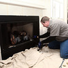 12-7-13<br /> Heartland-Fireplace insert Schlemmer Bros.<br /> Dennis Kochenour of Schlemmer Brothers replaces a gas insert in a fireplace.<br /> KT photo | Kelly Lafferty