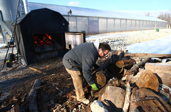 12-10-13<br /> Green River Greenhouse<br /> Daniel Emery loads cut wood into the wood furnace outside of the Green River Greenhouse north of Peru.<br /> KT photo | Kelly Lafferty