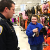 12-14-13<br /> Shop with a cop<br /> Kenny Radabaugh, 11, looks to Officer James Organ for approval to get the camouflage gloves he wanted at Meijer during Shop4Kidz on Saturday.<br /> KT photo | Kelly Lafferty