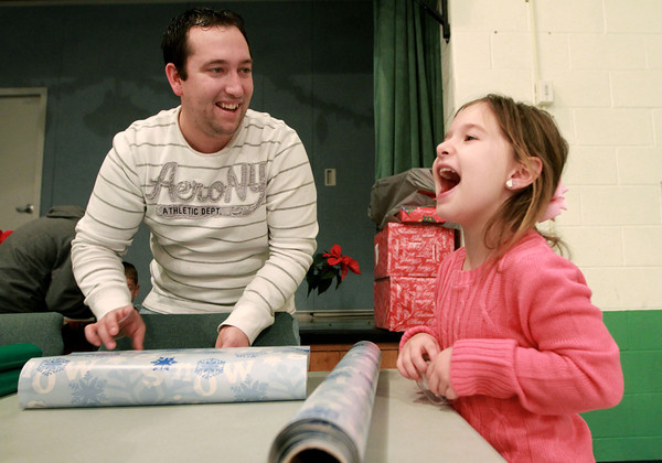 12-25-13<br /> Kokomo Urban Outreach Annual Christmas Blitz<br /> Joe Brown and his 6-year-old daughter Alivia, laugh together as they wrap presents on Christmas day during Kokomo Urban Outreach's Annual Christmas Blitz.<br /> KT photo | Kelly Lafferty