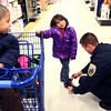 12-14-13<br /> Shop with a cop<br /> Officer Cameron Cunningham ties the shoe of 5-year-old Florencia Dillinger as her 3-year-old brother Eli watches from the cart. They were at Meijer on Saturday morning for Shop4Kidz.<br /> KT photo | Kelly Lafferty