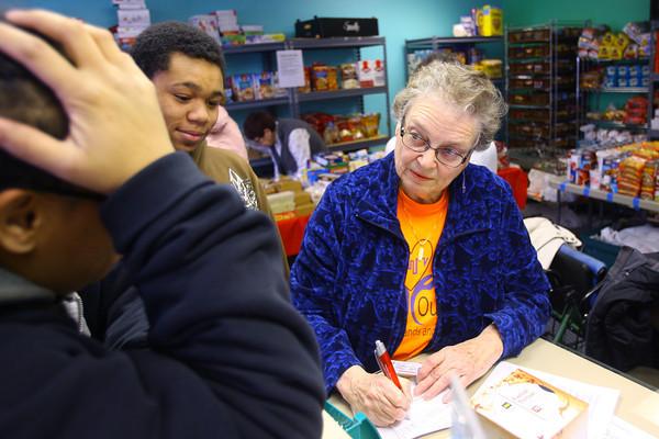 12-23-13   ---  Kokomo Urban Outreach volunteer Judy Whorley works with clients Yolanda Hillman and her son Devontez Harris, 15.<br />   KT photo | Tim Bath