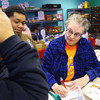 12-23-13   ---  Kokomo Urban Outreach volunteer Judy Whorley works with clients Yolanda Hillman and her son Devontez Harris, 15.<br />   KT photo | Tim Bath