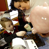 2/3/03<br /> CommunityFirst openened it doors for the first time on Monday. Ben Tracy, 5, was one of the first depositors. He was dumping his different piggy banks into the change counting machine.<br /> Kt photo by Tim Bath