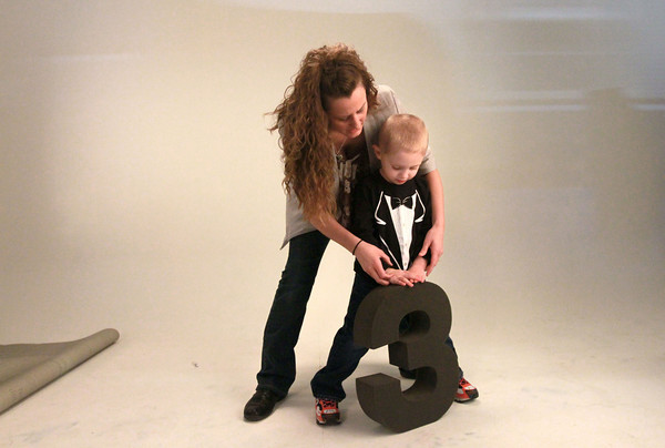 2-21-14<br /> Harmon photography in Peru<br /> Photographer Bridgette Harmon-Smith shows 3-year-old Hudson Sites how to pose with the number 3 in Harmon Photography studio in Peru.<br /> KT photo | Kelly Lafferty