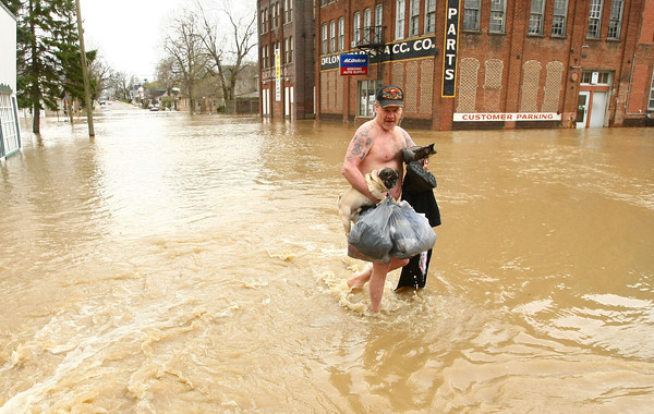 4-19-13<br /> Mike Trine carries his dog and clothes out of the flood water on South Union Street just south of the Wildcat Creek. He walked out then put on his dry clothes.<br /> KT photo   Tim Bath