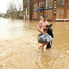 4-19-13<br /> Mike Trine carries his dog and clothes out of the flood water on South Union Street just south of the Wildcat Creek. He walked out then put on his dry clothes.<br /> KT photo | Tim Bath