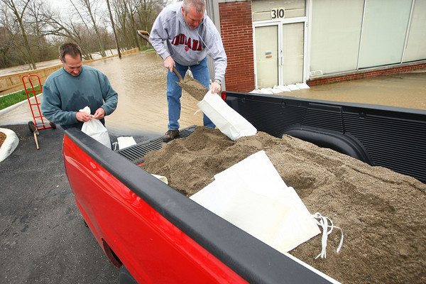 4-19-13<br /> Flooding throughout Kokomo and Howard County due to over 4 inches of rain. Owner of Scott Lithography at 310 South Union street, Scott Hemmberger and Terry Finley bag sand to put in front of the doors of the business to stop the water.<br /> KT photo   Tim Bath