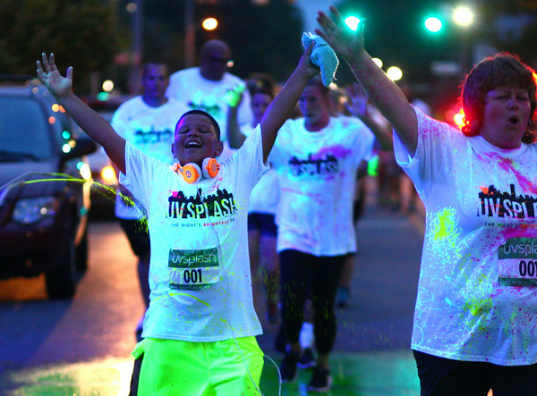 8-1-14<br /> Glo in the 'Mo, UV Splash by Color Dash and the Kokomo Family YMCA <br /> Runners and walkers raise their arms up to get sprayed with UV water at the station on Sycamore and Buckeye during Glo in the 'Mo, a UV Splash fundraiser for the YMCA.<br /> Kelly Lafferty | Kokomo Tribune
