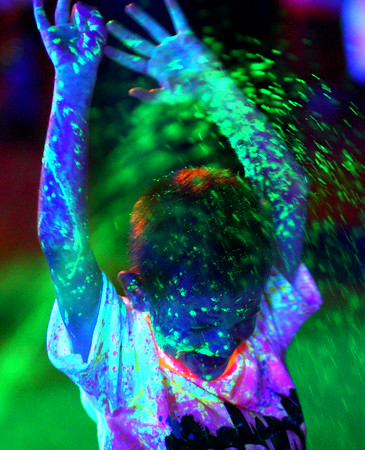 8-1-14<br /> Glo in the 'Mo,<br /> A participant gets sprayed by the UV Splash water at the finish line of Glo in the 'Mo, a 5K benefiting the Kokomo YMCA.<br /> Kelly Lafferty | Kokomo Tribune