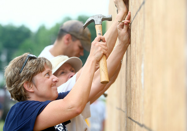 7-12-14<br /> Habitat for Humanity Apostles Build<br /> Ann Taylor of Oakbrook hammers on the outside of 1921 S. Bell Street during Habitat for Humanity's Apostle Build on Saturday.<br /> Kelly Lafferty | Kokomo Tribune