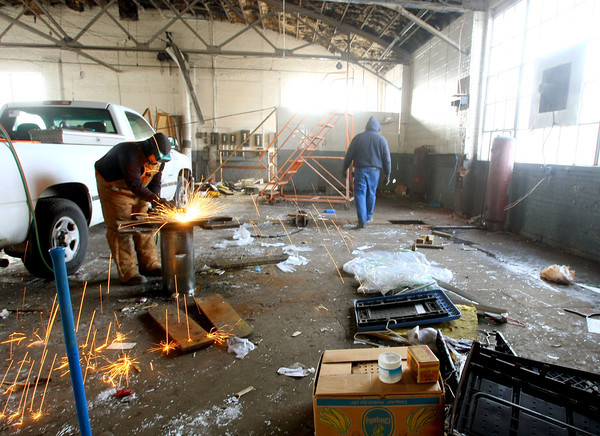 1-15-13<br /> Button Motors being leveled by City of Kokomo Street Department. Nick Dobbs uses a torch to cut the old lift station apart in the auto repair garage that faces Walnut Street.<br /> KT photo | Tim Bath