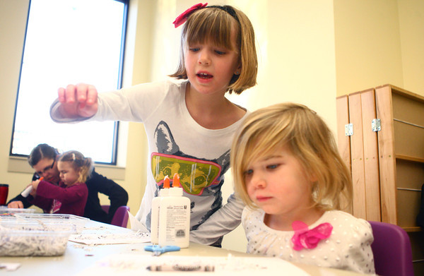 1-11-13<br /> After school crafts<br /> 4-year-old Ava Federspill's big sister Mia Federspill, 7, helps her find pieces to glue onto her snowman craft at the library on Friday afternoon.<br /> KT photo | Kelly Lafferty
