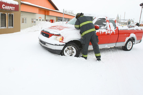 1-7-14   --- Snow and cold continues with schools closed and roads covered with snow and ice. A kokomo firefighter checks on a car that looks to be abandoned on north Washington Street. -- <br />   KT photo | Tim Bath