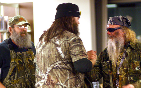 1-3-14   --- Duck Dynasty night at the Kokomo Howard County Public Library. Ron Swipe dressed as Si, Luke Stone dressed as Jase and Wayne Beckom dressed as Phil great each other as they check in for the contest. -- <br />   KT photo | Tim Bath
