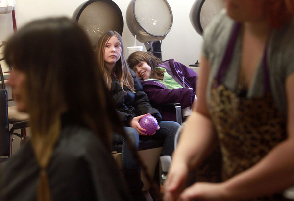 1-19-14<br /> Camilla Chesshir gets hair cut to donate it to make a wig for a co-worker who has cancer<br /> Camilla Chesshir's daughter April (right) and her friend Hannah Williams watch as Chesshir gets her hair cut at Beauty Buzz. April also got fourteen inches cut off her hair to donate.<br /> KT photo | Kelly Lafferty