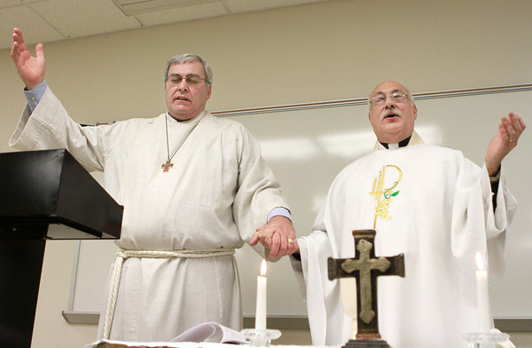 1-12-14<br /> Christ the King Anglican Church<br /> Brian Shone and Father Michael Henry hold hands as they sing The Lord's Prayer during Christ the King Anglican Church's Sunday service at IUK's observatory lecture hall.<br /> KT photo | Kelly Lafferty