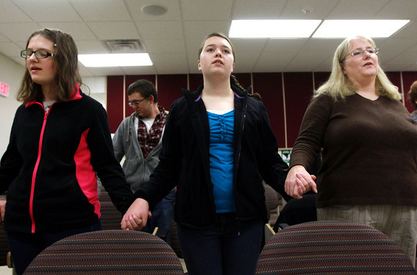 1-12-14<br /> Christ the King Anglican Church<br /> From left: Claudia Smith, Kerry Orttel, and Mindy Orttel hold hands as they sing The Lord's Prayer during Christ the King Anglican Church's service in IUK's observatory lecture hall on Sunday morning.<br /> KT photo | Kelly Lafferty