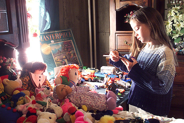 12/25/99<br /> Julia Dawn Smith, age 9, looks through some of the toys children were able to choose from as Christmas presents at the Favors' holiday dinner.  Adults were able to pick out clothing and other small items for themselves.<br /> KT photo by Sarah Stefko