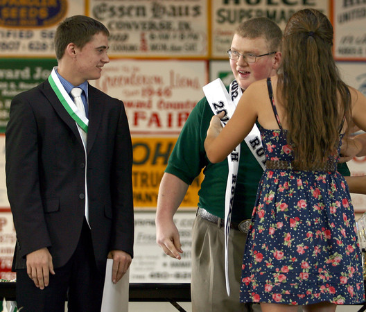 7-13-12<br /> HC Fair 4h awards<br /> Joshua Maurer and Austin Richard are becoming 4-H Royalty after collecting the most money in the penny votes during the fair. The money raised is used fro the 4-H Junior Leaders Scholarship Fund. Peyton Hite puts a sash on Richard.<br /> KT photo | Tim Bath
