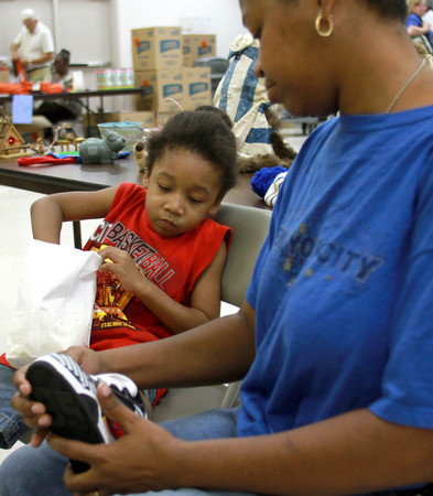 7-31-12  <br /> UAW Local 685 partnered with the United Way to give out school supplies<br /> Rachelle Ford helps her son JaMerion Holloway, 5, try on shoes as he eats popcorn at UAW Local 685.<br /> KT photo | Kelly Lafferty