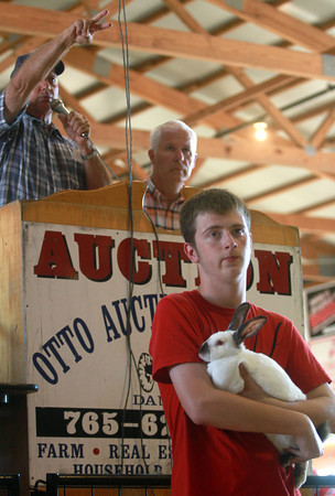 7-12-12<br /> 4H auction at Howard County Fair<br /> Jarren Mantz holds his rabbit in the auction ring as Auctioneer Mike Clair auctions it off behind him.<br /> KT photo | Kelly Lafferty
