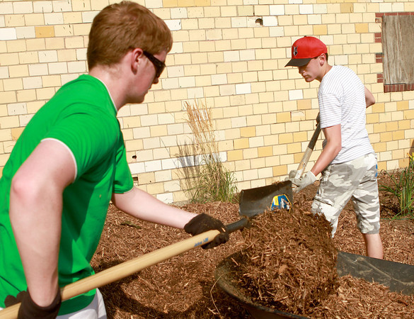 7-7-12<br /> A Scottish Youth Group partners with Grace United Methodist Church to beautify the Industrial Heritage Trail along Main and Markland.<br /> 18-year-old Fraser Cosgrove (left) worked with 16-year-old Gareth Scott-Dodd to shovel mulch into a wheelbarrow on Saturday morning. The two were part of a youth group from Scotland who partnered with Grace United Methodist Church in Kokomo to help beautify the trail walk.<br /> KT photo | Kelly Lafferty