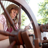 7-21-12<br /> Makers Art Market<br /> Rebecca Miller uses a spinning wheel to make yarn on Saturday morning at the Makers Arts Market. Miller taught herself how to use a spinning wheel by instructional DVD's. <br /> KT photo | Kelly Lafferty