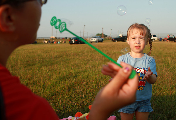 7-4-12  <br /> Fourth of July at Fairgrounds<br /> 3-year-old Elizabeth Lane catches bubbles from her mom Amanda Lane as they wait for fireworks on Wednesday evening at the Howard County Fairgrounds.<br /> KT photo | Kelly Lafferty